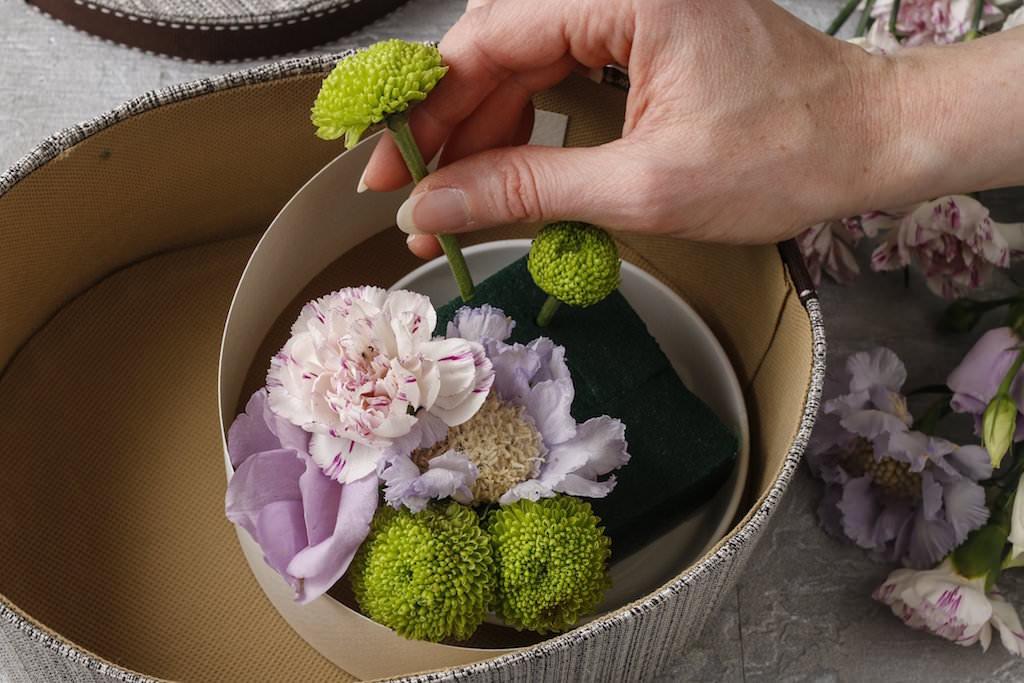 1.スイーツを入れるスペースを確保しつつ、箱のサイズに合わせてオアシスをカットします。水を張ったボウルにオアシスを浸して十分に吸水させ、オアシスベースやプラスチックのケースに入れ、箱の中に入れます。 2. スイーツの入るスペースとオアシスとの間に仕切りをつくり、短く切った花を挿していきます。水揚げをよくするために花を切る時は切り口を斜めにしましょう。
