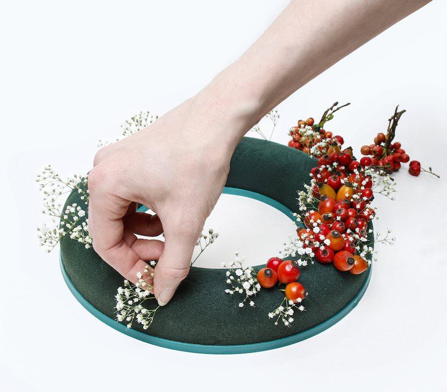 2. まず、実をある程度の束にして、一周ざっくり挿していきます。赤い実に加え、カスミソウを少し足します。フワフワした質感が艶やかな赤い実の美しさを際立たせてくれます。