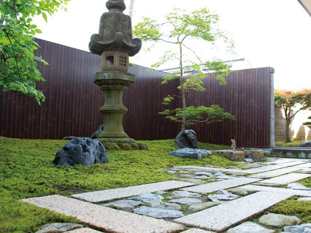 こげ茶色をバックに、苔(こけ)が映える和風の庭