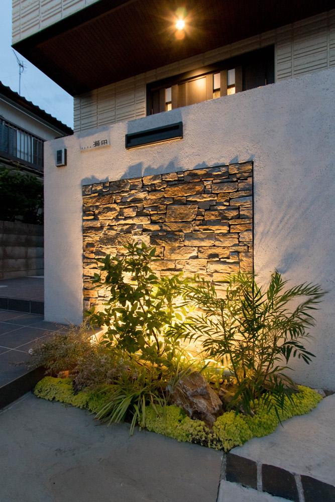 表札下の石の壁面を下から照らすことで、凹凸感が浮かびあがる