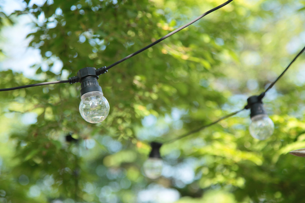 ガーデンのテーブルを覆う木々にガーデン用のライトが吊るされている