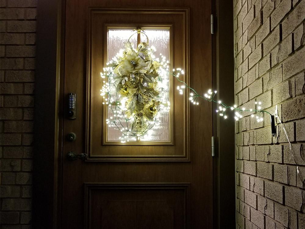 玄関では、ドアにグリーンのガーランドを吊るし、ストリングライトを組み合わせる