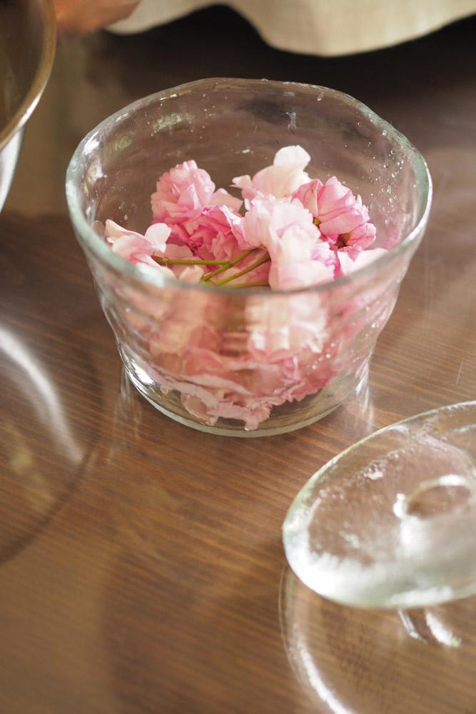 ガラス容器に桜を丁寧に入れる