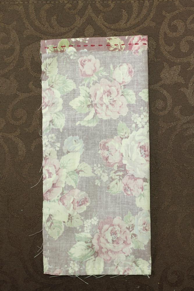 上部分を2つ折りにし、待ち針で留めて並縫いをしたのち、布を中表にしてはじを縫う