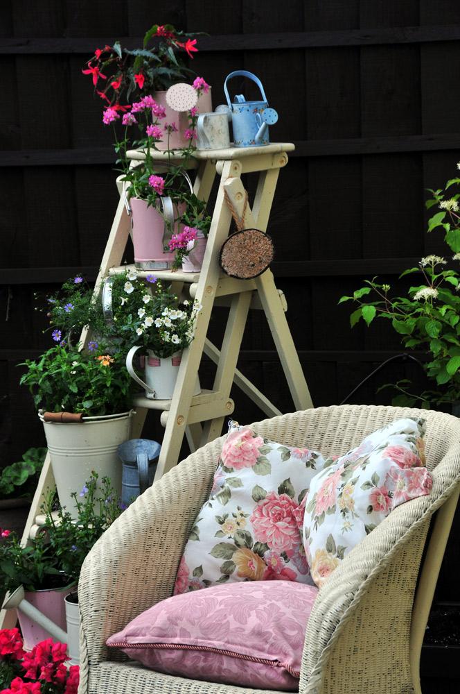 ベランダなど限られた空間では脚立も植物の棚に応用できる。ガーデンチェアと色を揃えて塗装し、統一感を。claire norman/Shutterstock.com